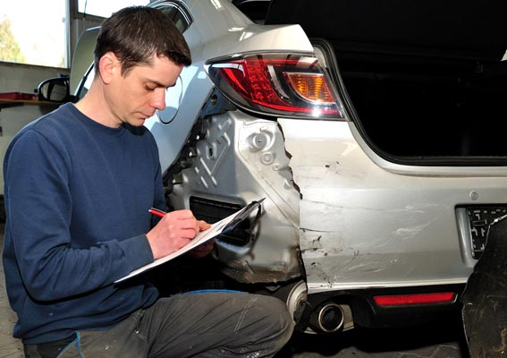 claims adjuster taking notes on the vehicle damage of a client
