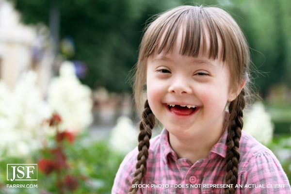 smiling child outside with double braids and Downs Syndrome