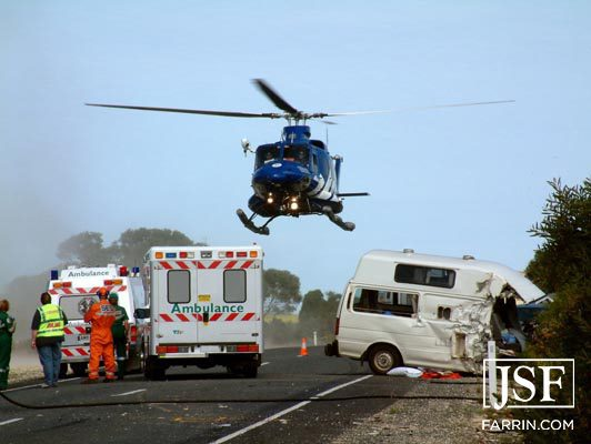 medical helicopter about to land near an ambulance and car accident scene