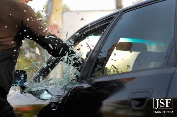 thief shattering the glass of a driver's side car window