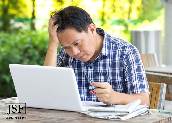 confused man looks at insurance policy on a laptop