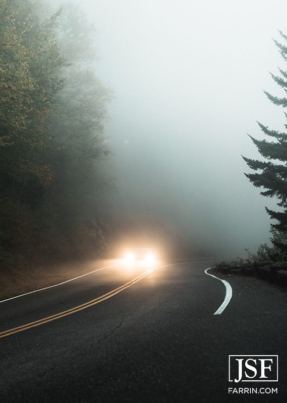 Car on a road in a misty forest with its headlights on.