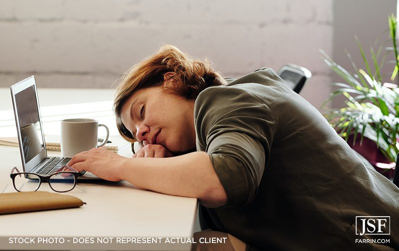 Woman falling asleep on her laptop due to insomnia.