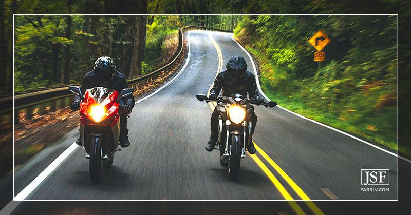 Two motorcyclists biking in the wrong lane on a narrow, winding forest road.