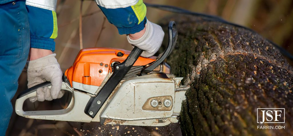 An emergency worker saws a tree that fell on a power line