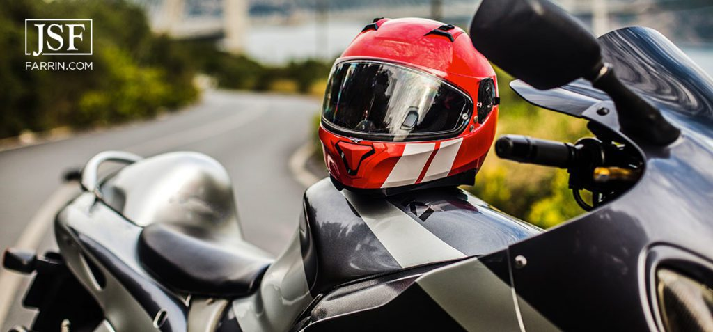 A grey black motorcycle and a red helmet