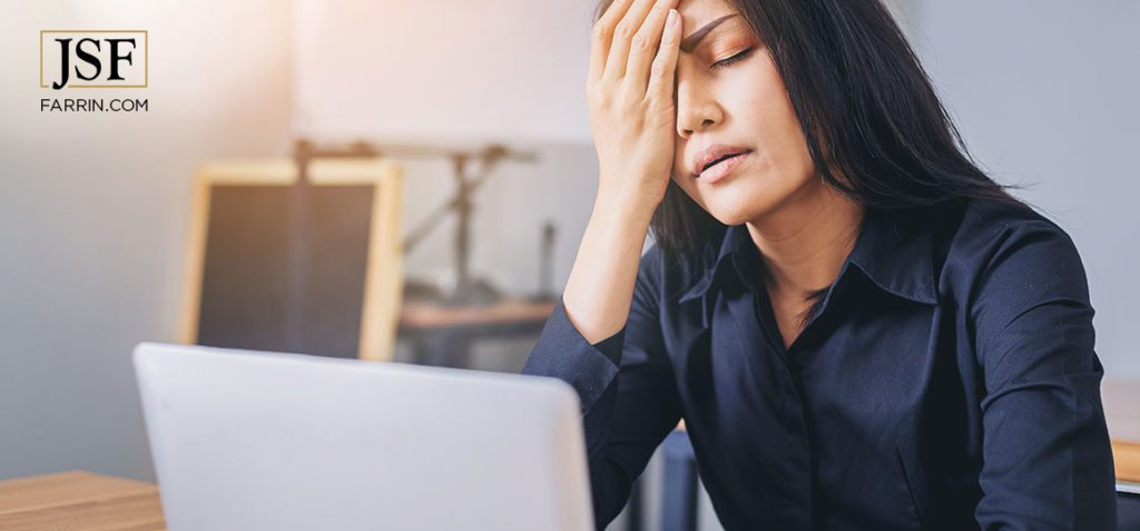 Woman rest face on hand while filling out workers' compensation info on her laptop