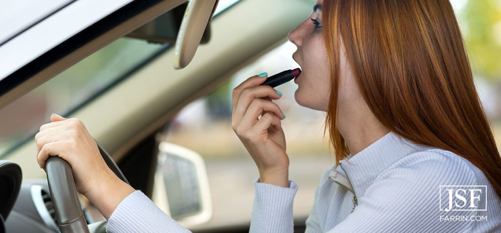 Close up of a young redhead woman driver correcting her makeup