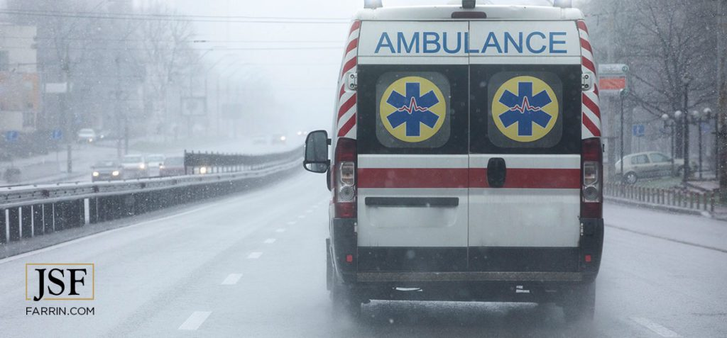 Ambulance moving down the street at high speed under the rain