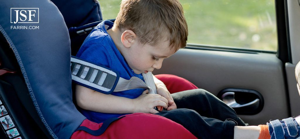 Little boy buckled up with seatbelt inside the car