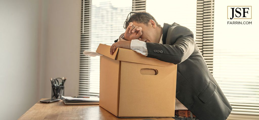 Man in suit resting head on hands over a box of his belongings