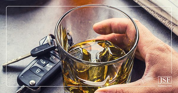 A hand grabbing a glass of whiskey next to car keys, representing drunk driving.