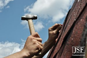 roofer hammering a nail into shingles