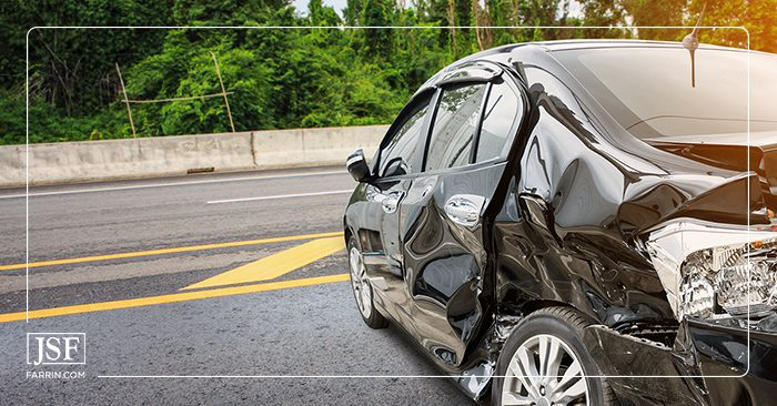 A wrecked black car on the road near a bridge barrier after a crash.