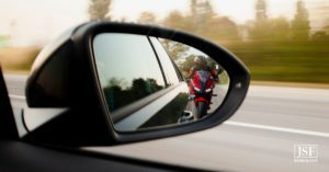 Motorcycle driver reflection in the side-view mirror of a car driving on a Durham road.