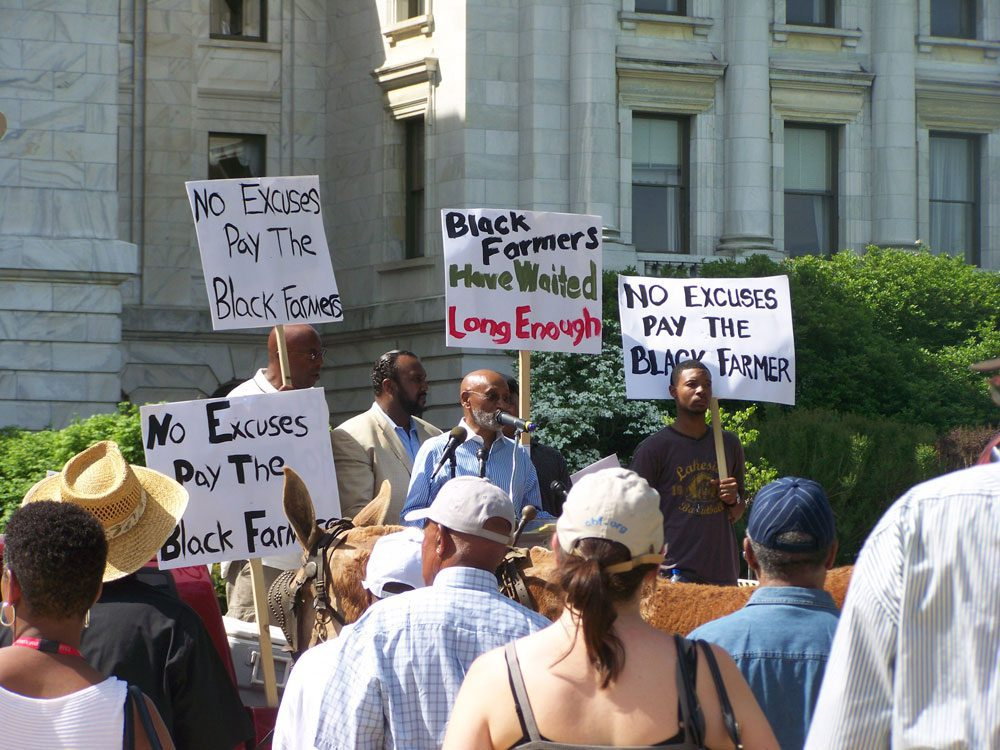 Protestors with signs for the Pigford II Black Farmers case