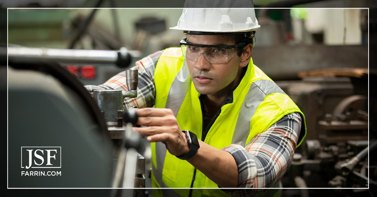 Industrial worker operating machine while wearing goggles to avoid potential eye injuries.