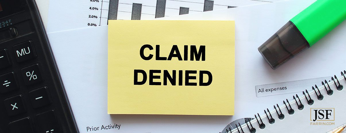 Denied form label laying on a desk. If your claim is denied, you have the right to request a hearing