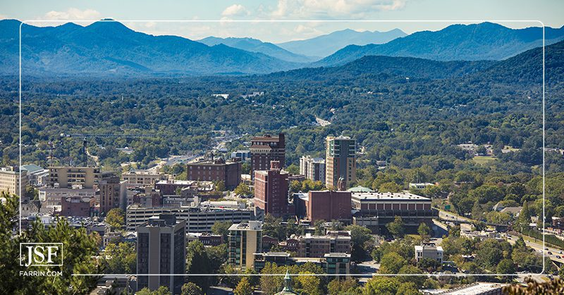 Aerial drone view of the city of Asheville, North Carolina, with the Blue Ridge Mountains in the background.
