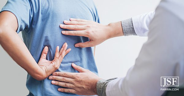 A chiropractor placing their hands on a patient's back.