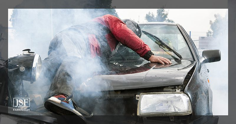 A motorcyclist laying on the hood of a car after impact with his arm outstretched.