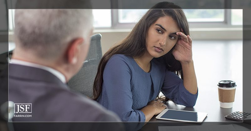 A frustrated woman holds her head in her hand during stressful negotiations with an insurance adjuster.