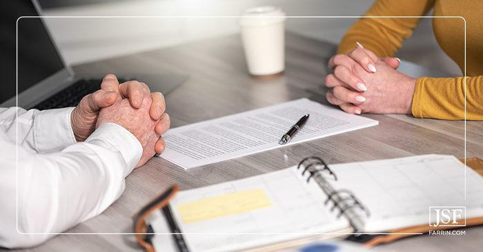 A business man and woman with clasped hands negotiating paperwork in an office.