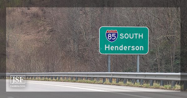 A green highway sign for interstate 85 (I-85) South and Henderson in North Carolina.