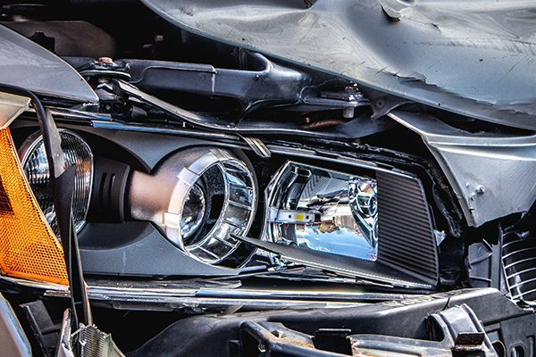 Close up of a smashed car headlight and hood after an accident.