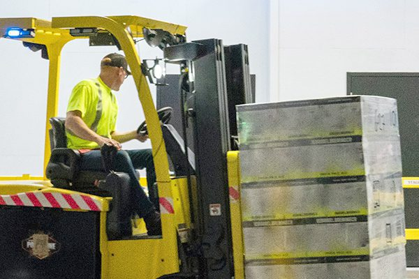 Man in a high vis shirt driving a yellow forklift carrying a pallet in a warehouse.