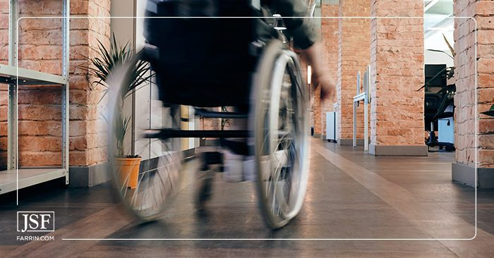Person moving quickly on a wheelchair through brick columns in a hallway.
