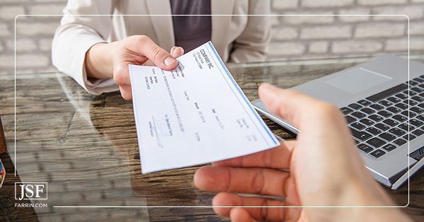 Person being handed a check for their workers' compensation settlement.
