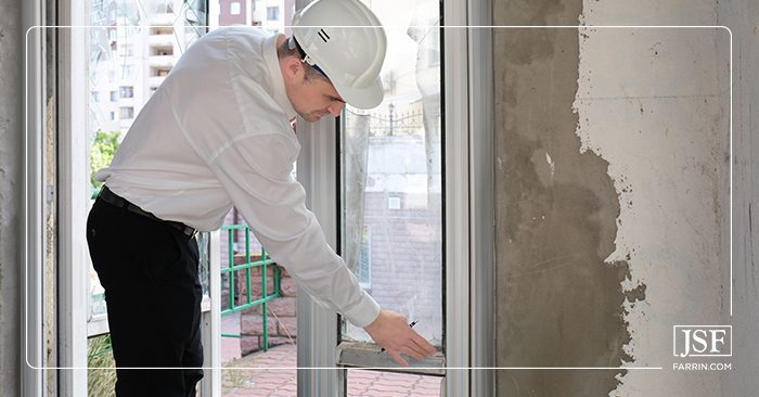 Insurance adjuster in a white hard hat inspecting a water damaged wall in a house.