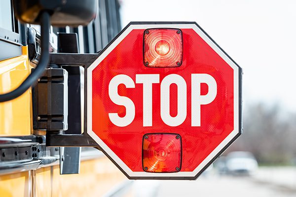 Blinking extended stop sign on the side of a yellow school bus.