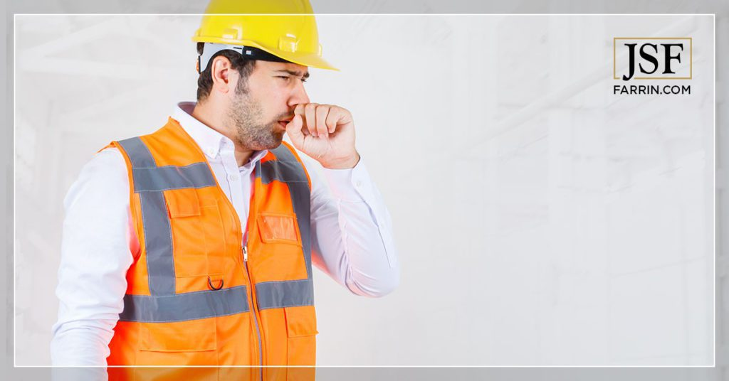 Industrial worker covering his face while coughing.