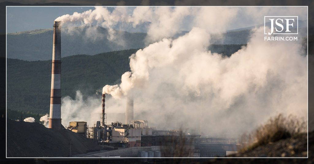 Exterior view of paper mill pipes emitting a considerable amount of air pollution.