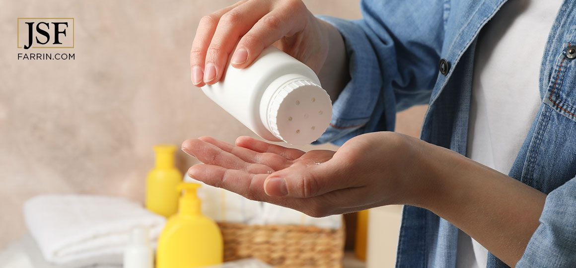 Mom applying talcum powder into her hand that may contain asbestos