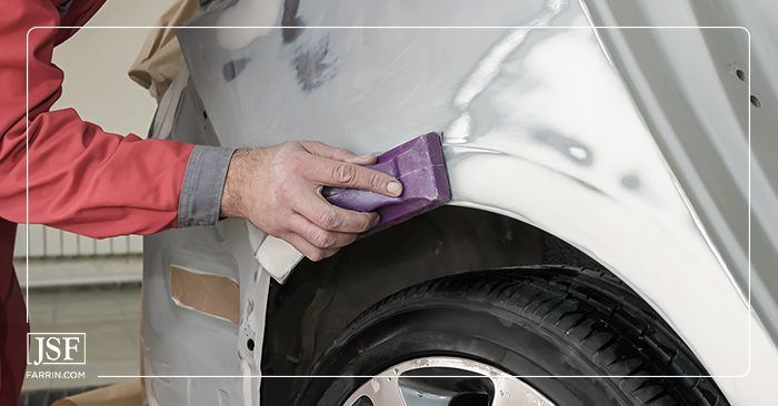Close up of a person sanding a car for painting during collision repair.